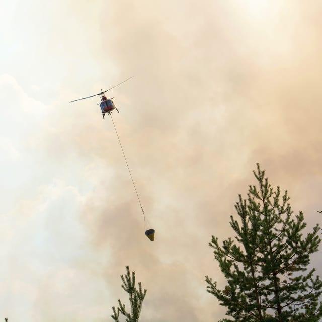 Helikopter släcker skogsbrand